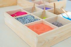 Una variedad de arena del color puso en una pequeña bandeja hecha de la madera usada para enseñar a arte Imagen de archivo