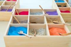 Una variedad de arena del color puso en una pequeña bandeja hecha de la madera usada para enseñar a arte Foto de archivo