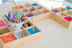 Una variedad de arena del color puso en una pequeña bandeja hecha de la madera usada para enseñar a arte Imagenes de archivo