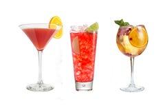 Una variedad de bebidas alcohólicas, de bebidas y de cócteles en un fondo blanco Tres bebidas en diversos vidrios de cristal con imagen de archivo