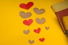 Una variedad de corazón y de libros en un fondo amarillo foto de archivo