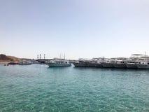 Una variedad de motor y de veleros, barcos, trazadores de líneas de la travesía se colocan en un muelle en el puerto contra la pe Imagenes de archivo