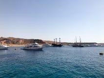 Una variedad de motor y de veleros, barcos, trazadores de líneas de la travesía se colocan en un muelle en el puerto contra la pe Foto de archivo
