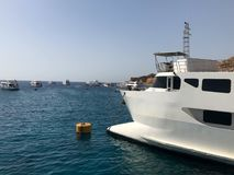 Una variedad de motor y de veleros, barcos, trazadores de líneas de la travesía se colocan en un muelle en el puerto contra la pe Fotografía de archivo