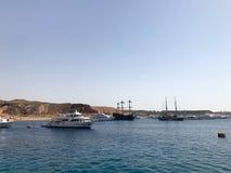 Una variedad de motor y de veleros, barcos, trazadores de líneas de la travesía se colocan en un muelle en el puerto contra la pe Fotografía de archivo libre de regalías