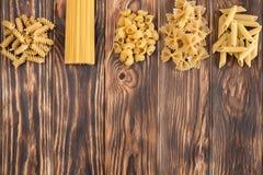 Una variedad de variedades de pastas en una tabla de madera hermosa Imagen de archivo libre de regalías