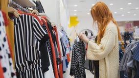 Una variedad de vestidos en una tienda de ropa del ` s de las mujeres enmascarado Imágenes de archivo libres de regalías