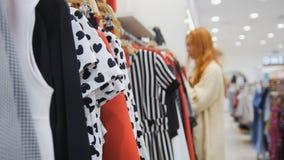 Una variedad de vestidos en una tienda de ropa del ` s de las mujeres enmascarado Foto de archivo