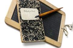 Una vecchi ardesia, portapenne e quaderno, imparare scrivono fotografie stock