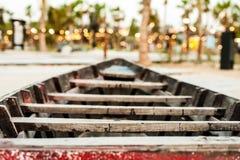 Una vecchia barca di legno sulla spiaggia sotto la palma Fotografia Stock