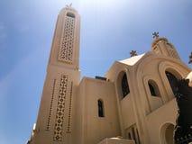 Una vecchia bella chiesa cristiana ortodossa di pietra bianca beige è un posto per pregare a Dio con un incrocio con le finestre  fotografia stock