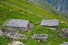 Una vecchia capanna alpina di pietra abbandonata nelle montagne immagini stock