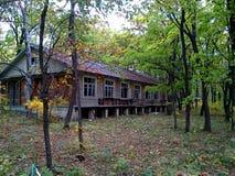 Una vecchia casa abbandonata in un campo nella foresta di autunno fotografie stock