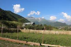 Una vecchia casa di campagna con una vista delle montagne nevose nei precedenti Immagine Stock Libera da Diritti