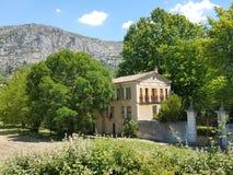Una vecchia casa gialla nelle alpi della Provenza del francese circondate dagli alberi e una montagna enorme nei precedenti Fotografia Stock Libera da Diritti
