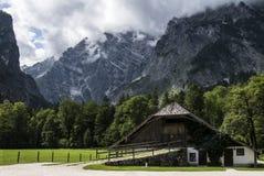 Una vecchia casa intorno ad una foresta dei pini verdi sotto una montagna Fotografia Stock Libera da Diritti