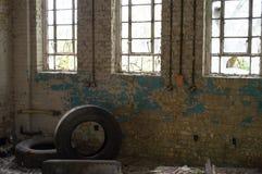 Una vecchia costruzione abbandonata con le finestre, la pittura della sbucciatura e tre rotti ha usato i pneumatici immagine stock libera da diritti