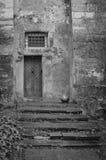 Una vecchia costruzione con un a porta chiusa in bianco e nero Fotografia Stock