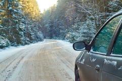 Una vecchia guida di veicoli lungo una strada di inverno Fotografia Stock Libera da Diritti