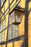 Una vecchia lanterna metallica che pende da un muro di mattoni giallo a Copenhaghen, Danimarca fotografie stock