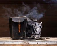 Una vecchia macchina fotografica della foto su una priorità bassa scura Fotografia Stock
