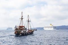 Una vecchia nave accanto a parecchie grandi navi da crociera vicino al porto di Fira, Santorini, Grecia fotografia stock libera da diritti