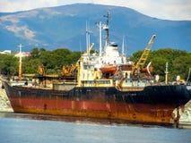 Una vecchia nave arrugginita imbarcata in secca vicino alla riva di Mar Nero Immagini Stock Libere da Diritti