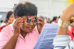 Una vecchia prova della donna dell'Asia osserva dalle strutture di prova immagini stock