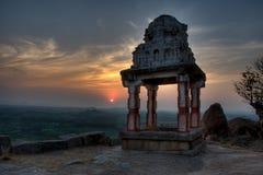 Una vecchia rovina di un tempio indù nella siluetta dei semi con il tramonto nel fondo Fotografia Stock
