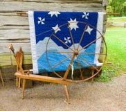 Una vecchia ruota di filatura e una trapunta su esposizione ad un sito storico nella Virginia immagini stock