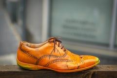 Una vecchia scarpa arancio su una plancia di legno Fotografia Stock Libera da Diritti