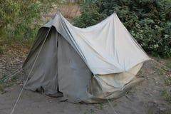 Una vecchia tenda dell'URSS su un picnic in una foresta su una sabbia con erba immagini stock