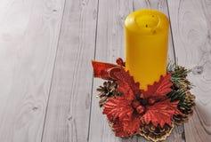 Una vela amarilla y un pino del Año Nuevo enrruellan en un viejo fondo de madera Imagen de archivo