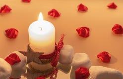 Una vela de iluminación con las rosas fotos de archivo libres de regalías