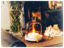 Una vela eléctrica que quema debajo de un vidrio en la tabla fotografía de archivo