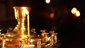 Una vela en la palmatoria del templo cristiano almacen de video