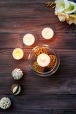 Una vela en un florero de cristal, una decoración y diversos elementos interesantes Velas de quema Foto de archivo libre de regalías