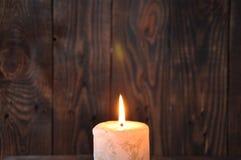 Una vela grande quema en la oscuridad en un fondo de madera de la textura fotos de archivo