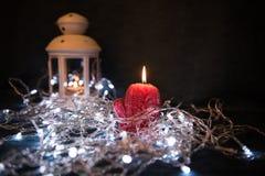 Una vela roja con las luces de la Navidad en la luz atmosférica Imagenes de archivo