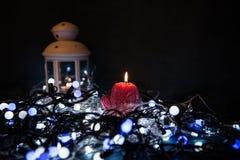Una vela roja con las luces de la Navidad en la luz atmosférica Fotografía de archivo