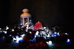 Una vela roja con las luces de la Navidad en la luz atmosférica Imagen de archivo libre de regalías