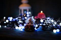 Una vela roja con las luces de la Navidad en la luz atmosférica Fotos de archivo