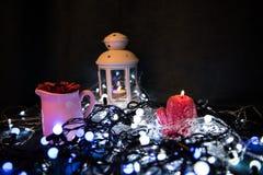 Una vela roja con las luces de la Navidad en la luz atmosférica Imágenes de archivo libres de regalías