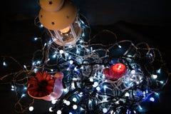 Una vela roja con las luces de la Navidad en la luz atmosférica Foto de archivo
