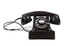 Una vendimia, teléfono negro en un fondo blanco Fotos de archivo libres de regalías