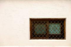 Una ventana con las cubiertas de la reja en la pared foto de archivo