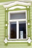 Una ventana de una casa de madera del condado adornada por los marcos blancos Imagenes de archivo