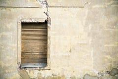 Una ventana de madera amarilla sucia marrón en una fachada agrietada rota amarilla gris de una casa abandonada abandonada Fotos de archivo