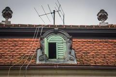 Una ventana del tejado de la corona con la antena y los alambres foto de archivo