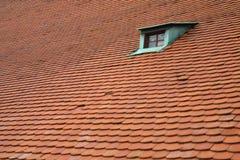 Una ventana verde en una azotea roja Foto de archivo libre de regalías